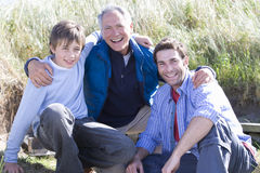 Portrait of multi-generation family crouching on beach Royalty Free Stock Images