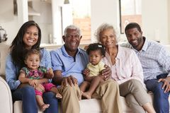 Portrait Of Multi-Generation Family Sitting On Sofa At Home With Baby Granddaughters stock images