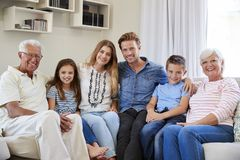Portrait Of Multi Generation Family Sitting On Sofa At Home Royalty Free Stock Photo