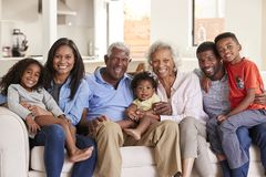 Portrait Of Multi-Generation Family Sitting On Sofa At Home Smiling At Camera stock photography