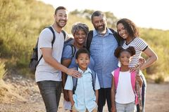 Portrait Of Multi Generation Family Wearing Backpacks Hiking In Countryside Together royalty free stock images