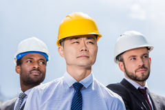 Portrait of multiathic group of professional architects in hard hats Royalty Free Stock Photo