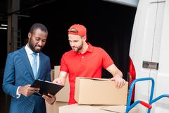 portrait of multicultural businessman and delivery man stock photo
