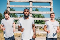 Portrait of multicultural soldiers practicing in obstacle run. On range royalty free stock image