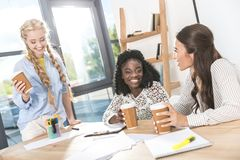 portrait of multicultural young businesswomen with coffee to go stock photos