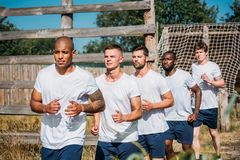 Portrait of multicultural young soldiers running. On range royalty free stock photo