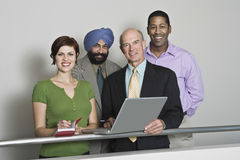 Portrait Of Multiethnic Businesspeople. Group portrait of smiling multiethnic businesspeople with laptop royalty free stock photography
