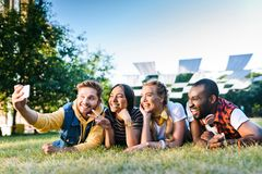 portrait of multiethnic cheerful friends taking selfie on smartphone while resting on green grass royalty free stock photos