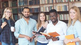 Portrait of multiethnic diverse friends pupils looking at page of interesting book in college library stock video