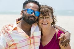 Portrait of multiethnic man and senior woman walking outdoors - Happy multiracial couple at beginning of love story - Integration stock image