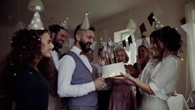 A portrait of multigeneration family with a cake on a indoor birthday party, confetti falling. stock video