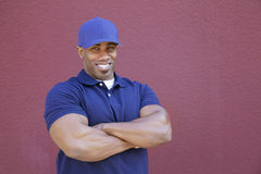 Portrait of a muscular African American delivery man with arms crossed over colored background Stock Photos