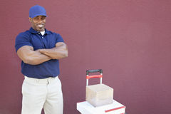 Portrait of a muscular African American man standing with arms crossed and handtruck over colored background Royalty Free Stock Photography