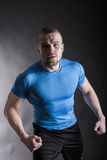 Portrait of a muscular aggressive young man standing in studio on black studio background Stock Photos