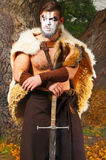 Portrait of a muscular ancient warrior with a sword. Ancient Barbarian in the woods Stock Photo