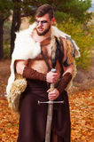 Portrait of a muscular ancient warrior with a sword. Ancient Barbarian in the woods Stock Images