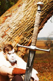 Portrait of a muscular ancient warrior. Sword in the foreground royalty free stock photo
