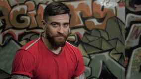 Portrait of muscular bearded male man athlete in red t-shirt sitting in cross fit