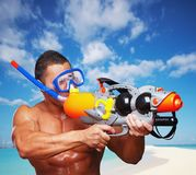 Muscular male with water gun. Portrait of muscular male on a beach with hight pressure water toy gun Royalty Free Stock Photo