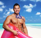 Portrait of muscular male in underwater scuba mask. Portrait of muscular male in underwater scuba mask holding pink water matress on a beach under blue sky Stock Photography