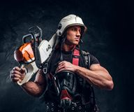 Portrait of muscular man with chainsaw and respirator. Muscular pensive man in helmet is looking away. He put his chainsaw on shoulder. With another hand he stock photos