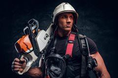Portrait of muscular man with chainsaw and respirator stock photo