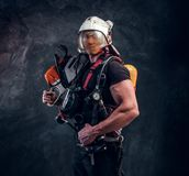 Portrait of muscular man with chainsaw and respirator royalty free stock photos