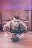 Portrait of muscular man doing pull up with medicine ball. At crossfit gym Stock Images