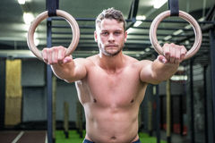 Portrait of muscular man doing ring gymnastics Stock Photo