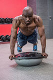 Portrait of muscular man exercising with bosu ball. In crossfit gym Royalty Free Stock Image
