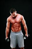Portrait of muscular man holding dumbbells Stock Images