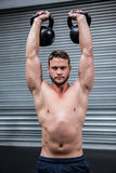 Portrait of muscular man lifting two kettlebells Royalty Free Stock Photo