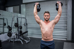 Portrait of muscular man lifting two kettlebells Stock Photo