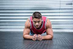 Portrait of muscular man in plank position. In crossfit gym Royalty Free Stock Photos