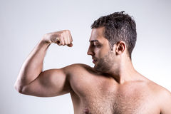 Portrait of muscular man pulling his bicep to show off Stock Images