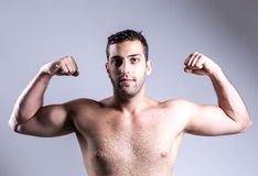 Portrait of muscular man pulling his bicep to show off Stock Photography