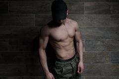 Portrait of Muscular Man Standing Near the Wall stock photo