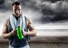 Portrait of muscular man standing with sipper water bottle against storms clouds Royalty Free Stock Photos
