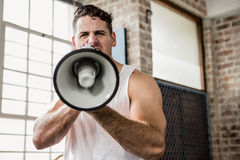 Portrait of muscular man talking through megaphone Royalty Free Stock Images