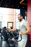 Portrait of muscular man training on special sport equipment Royalty Free Stock Images
