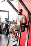 Portrait of muscular man training on special sport equipment Stock Photography