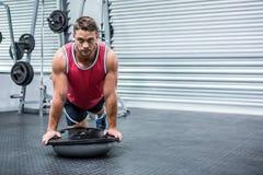 Portrait of muscular man using bosu ball Stock Images
