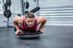 Portrait of muscular man using bosu ball. In crossfit gym Royalty Free Stock Photos