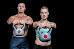 Portrait of muscular man and woman lifting kettlebells Royalty Free Stock Image