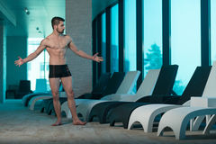 Portrait Of A Muscular Sexy Man In Underwear. Young Muscular Man Flexing Muscles By Swimming Pool And Sun Loungers Stock Photo
