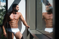 Portrait Of A Muscular Shirtless Model In Underwear. Portrait Of A Sexy Muscular Man In Underwear Looking Through Window Royalty Free Stock Images