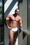 Portrait Of A Muscular Shirtless Model In Underwear. Portrait Of A Sexy Muscular Man In Underwear Looking Through Window Stock Photos