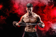 Portrait of muscular sportsman tearing metal chain.Black background. Royalty Free Stock Photo
