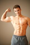 Portrait of muscular sporty man, he shows his biceps Stock Photos