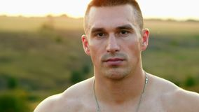 Portrait of muscular strong man after training looking at camera, sportsman with bare torso outdoors at sunset, sport. And motivation concept stock video footage
